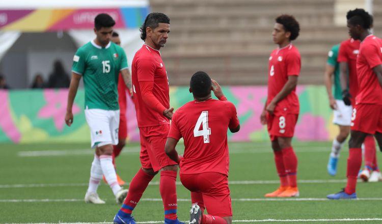 Manuel 'Cholo' Torres levanta a Emmanuel Chanis (4) de Panamá, luego del empate ante México en los Panamericanos. EFE