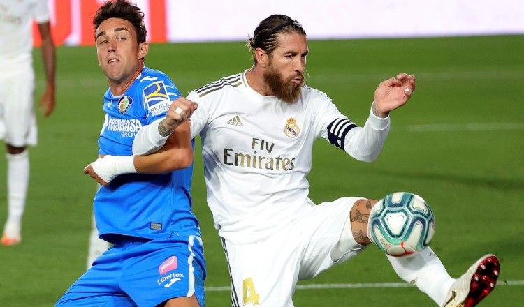 El defensa del Real Madrid, Sergio Ramos (der.) despeja el balón ante el delantero del Getafe, Jaime Mata. Foto:EFE