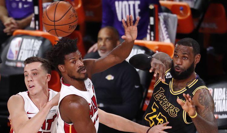 LeBron James realiza un pase de balón, ante la marca Jimmy Butler de los Heat. Foto:EFE