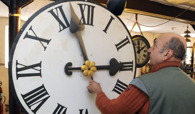 Peter Leonardy, examina un reloj fabricado alrededor del año 1900.
