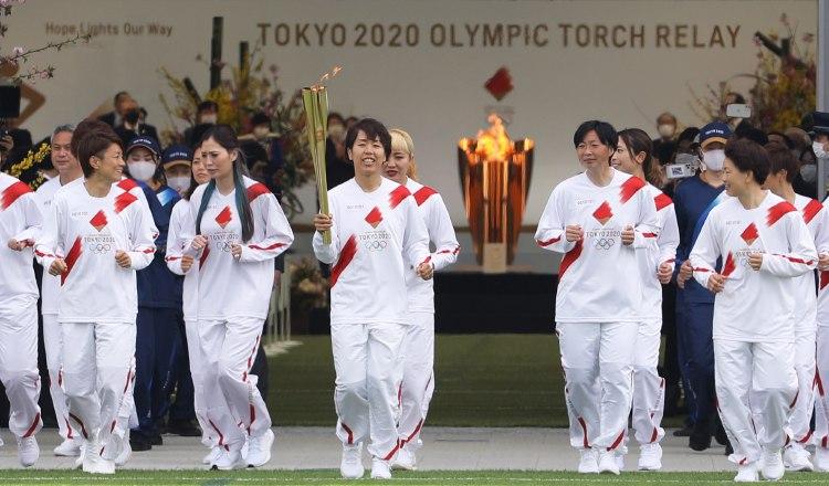 Azusa Iwashimizu (cent.) y otros miembros del equipo de fútbol femenino de Japón corren como portadores de la antorcha. Foto:EFE