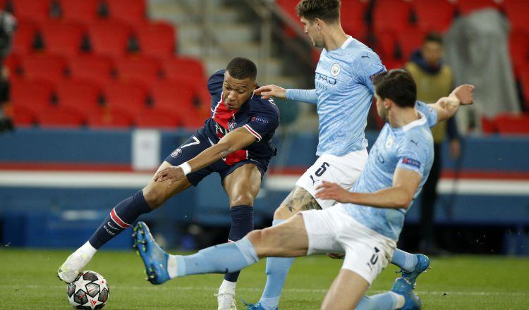 Kylian Mbappé del PSG intenta dominar el balón ante la marca de dos jugadores del Manchester City. Foto:EFE