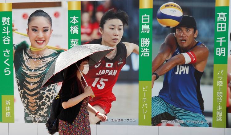 Un peatón protegida del sol y con una máscara en una publicidad de atletas en los Juegos. Foto:EFE