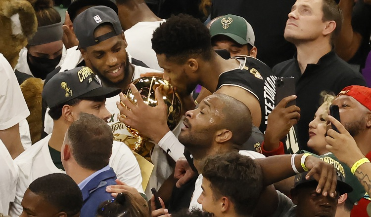 Giannis Antetokounmpo besa junto a Larry O'Brien el trofeo de campeón de la NBA. Foto.EFE