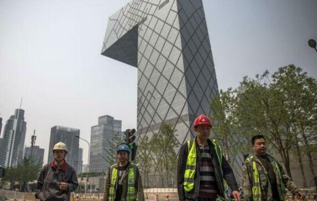 Trabajadores caminan por el distrito financiero de Pekín, en China, cuya economía siguió desacelerándose en el tercer trimestre. EFE