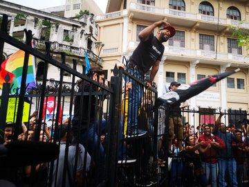 Los manifestantes se subieron a la cerca de la Asamblea Nacional para protestar en contra de las reformas constitucionales.