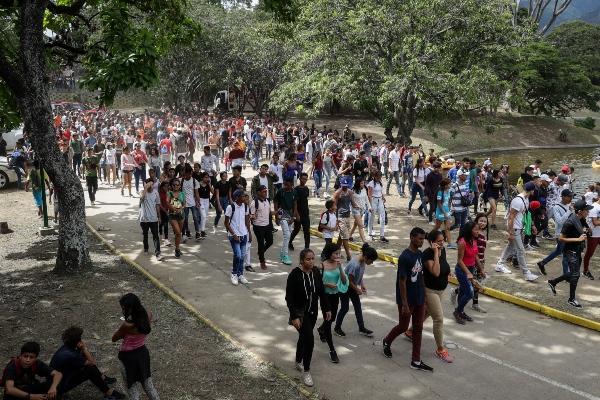 Personas cruzan una laguna tras salir de un concierto en las instalaciones del Parque Generalisimo Francisco de Miranda este sábado en Caracas. FOTO/EFE