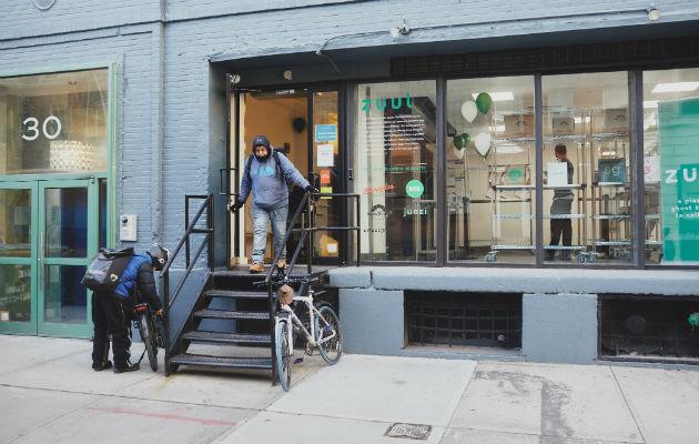Encargados del reparto de comida entran y salen de un local en Manhattan que maneja seis restaurantes. Foto / Andrew White para The New York Times.