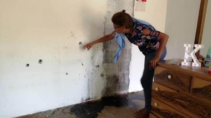 Luz Eneida Ledezma, madre de José Julio Ledezma, muestra los orificios de las balas en las paredes de la casa. Foto/Eric Montenegro.