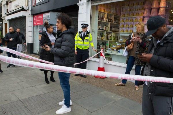 Un policía asegura el sitio de un incidente después de que un hombre haya sido baleado por la policía armada en una calle de Streatham, Londres. FOTO/AP