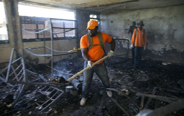Un rescatista recoge escombros dentro del orfanato incendiado. Foto: AP.