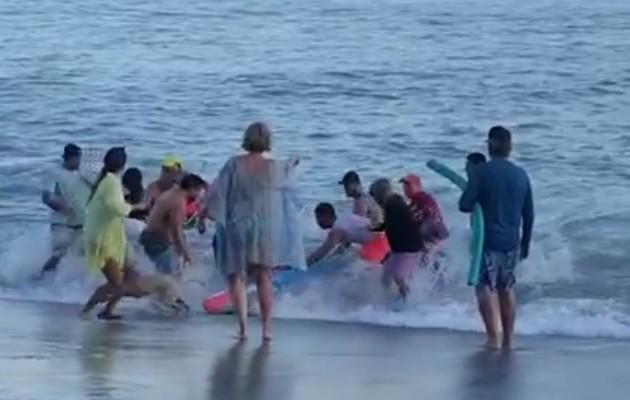 Momento en que un grupo de personas sacaba del mar a la adulta mayor.