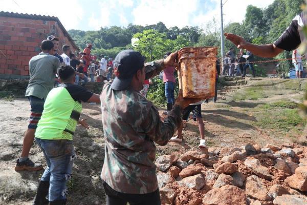 habitantes y bomberos buscando a los desaparecidos tras el derrumbe en el