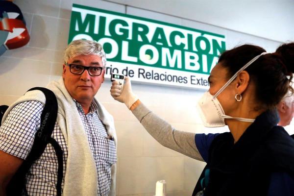 Funcionarios toman la temperatura de los ciudadanos que llegan al aeropuerto internacional El Dorado, como parte de la campaña de prevención y contención contra el coronavirus. FOTO/EFE