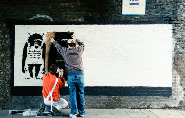 Banksy (izq.) y un asistente hacen un stencil en la calle Rivington en Londres a principios de los años 2000. Foto / Steve Lazarides.
