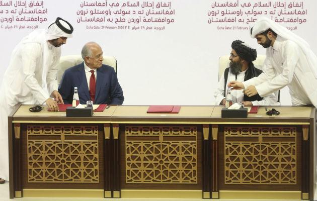 Zalmay Khalilzad, enviado de Estados Unidos, y el Mullah Abdul Ghani Baradar, líder talibán, firman un trato de paz en Qatar. Foto / Hussein Sayed/Associated Press.