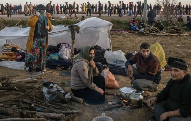 Migrantes descansan mientras cientos más hacen fila para comer en un cruce fronterizo de Turquía con Grecia. Foto / The New York Times.