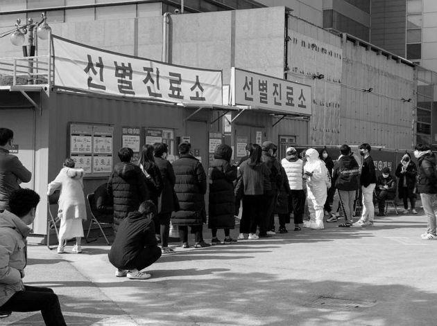 Decenas de pacientes hacen cola para describir sus síntomas y ser examinados en el exterior de la recepción especial instaurada en el Centro Médico Daegu, Corea del Sur. Foto: EFE.