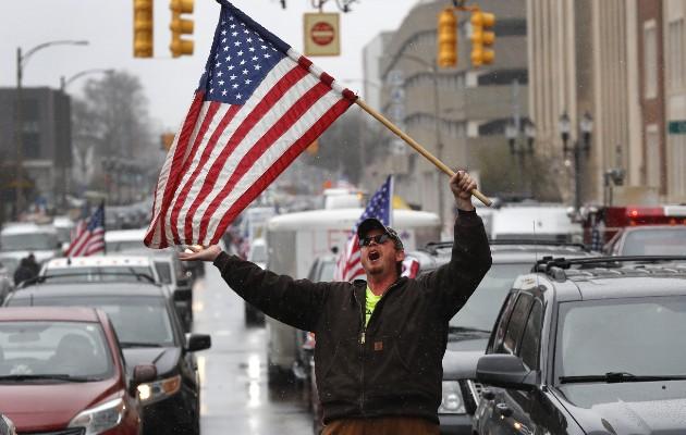 Un manifestante en Michigan entre una fila de autos pasando frente al Capitolio Estatal y tocando el claxon para protestar por los cierres. Foto / Paul Sancya/Associated Press.