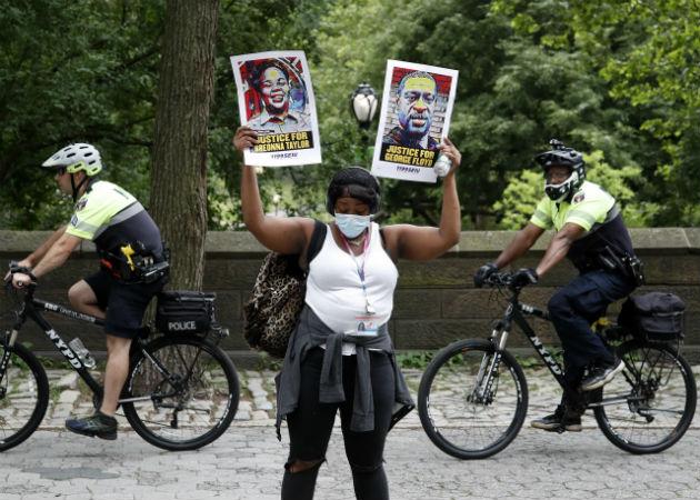 Una manifestante porta retratos de afroamericanos víctimas del racismo. Fotos: EFE.