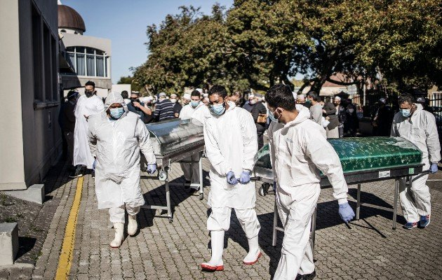 Enterradores cargan ataúdes tras un funeral para víctimas de coronavirus en Ciudad del Cabo en junio. La asistencia a funerales se limita a 50 personas. Foto / Marco Longari/Agence France-Presse — Getty Images.