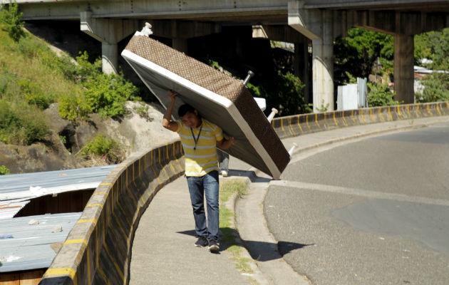 Un residente de la colonia La Betania, reubicaba ayer sus pertenencias ante el eventual desborde del río Choluteca en Tegucigalpa. Foto: EFE.