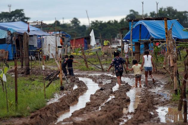 Niños recorren un camino lodoso en el terreno