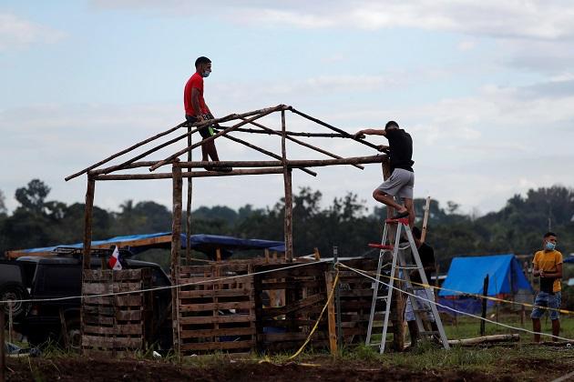 Un hombre construye una casa improvisada en el terreno
