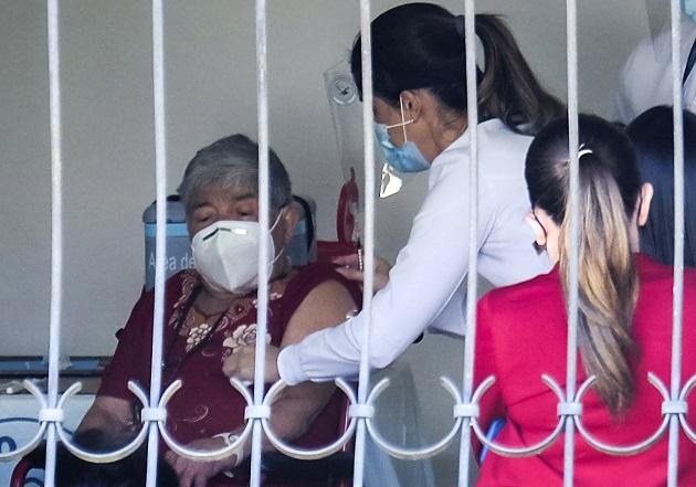 Personal del ministerio de Salud atiende a Elizabeth Castillo, quien fue la primera persona en ser vacunada contra la COVID-19 en Costa Rica, el 24 de diciembre. Foto: EFE