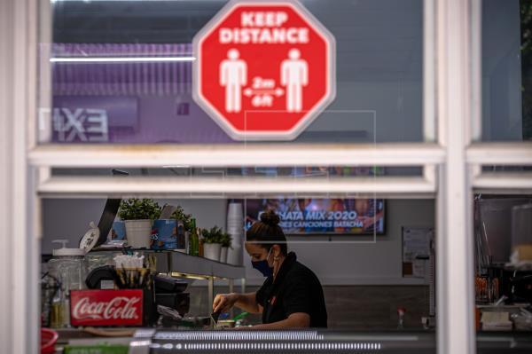 Una mujer trabaja en un local de comida que solo sirve por ventana, debido a la pandemia del coronavirus, en Miami, Florida. Foto: EFE
