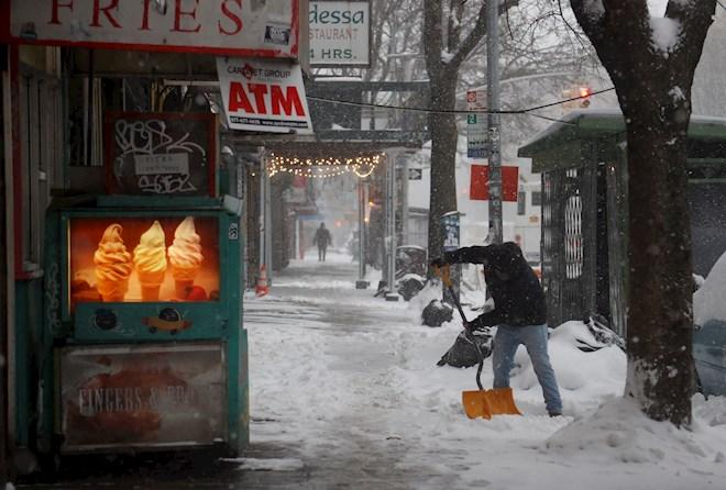 Un hombre quita nieve a lo largo de St. Mark's Place, durante una tormenta de nieve en Nueva York. Foto:EFE
