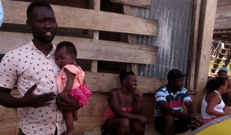 Un padre haitiano carga a su hija de cuatro meses en la comunidad de Bajo Chiquito, luego de realizar la caminata por el Tapón del Darién. Víctor Arosemena