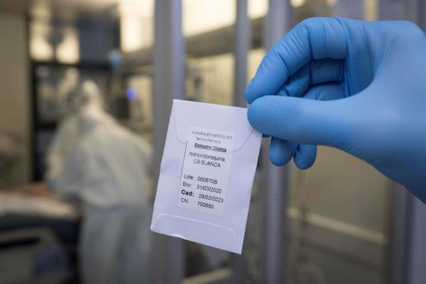 Una enfermera de una unidad de cuidados intensivos (UCI) muestra una dosis de hidroxicloroquina.