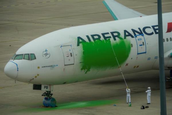 Activistas de Greenpeace pintan de verde un avión de Air France en el aeropuerto Charles de Gaulle para reclamar una reducción de vuelos.