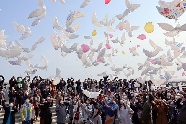 Personas lanzan globos con mensajes para las víctimas del devastador terremoto y tsunami de 2011 en Natori, Japón. Foto: EFE