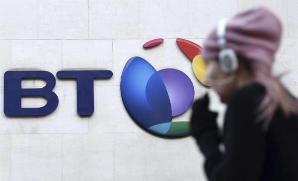 Un peatón camina junto al logotipo de la compañía British Telecom (BT) en su sede en Londres.