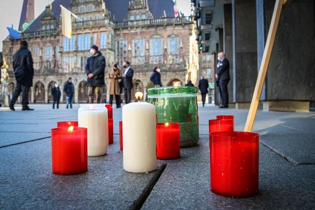 Velas encendidas reposan sobre el pavimento durante una ceremonia para conmemorar las muertes de coronavirus frente al parlamento estatal de Bremen. Foto: EFE