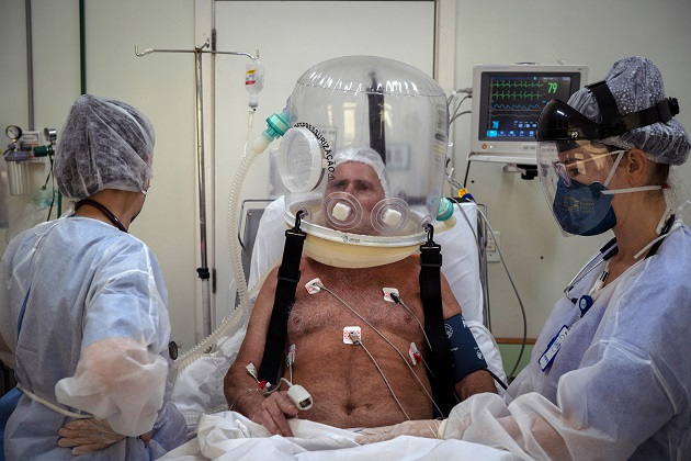 Trabajadores de la salud atienden con un casco burbuja a un paciente con la covid-19 en Brasil. Foto: EFE