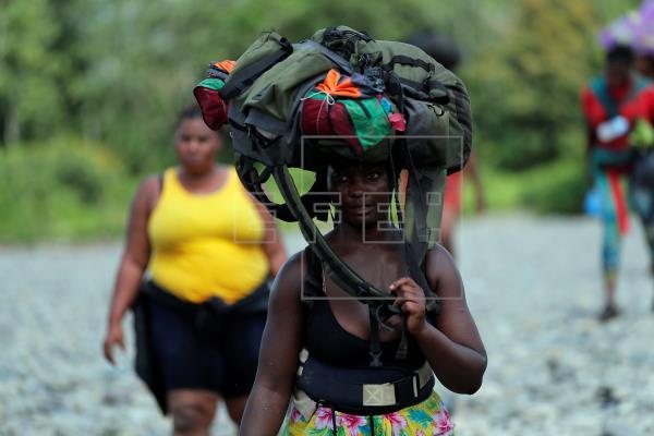 Una mujer migrante llega con su mochila en la cabeza, el 10 de febrero de 2021, a la comunidad de Bajo Chiquito, provincia del Darién (Panamá). Foto: EFE