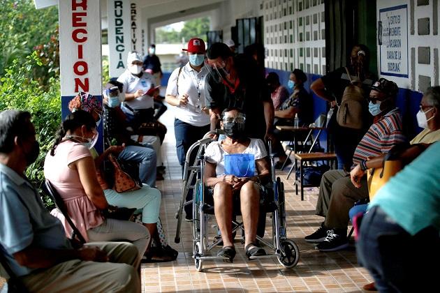 Varias personas esperan para recibir la primera dosis de la vacuna Pfizer contra la covid-19 en La Chorrera. Foto: EFE