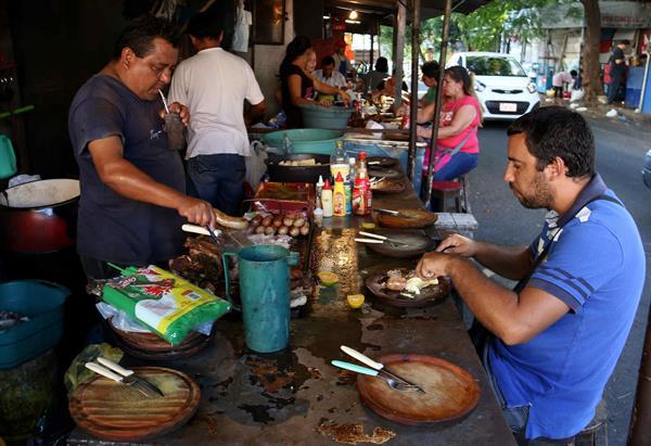 Fotografía del 18 de marzo de 2016 de varias personas comiendo en un mercado de Asunción, Paraguay.