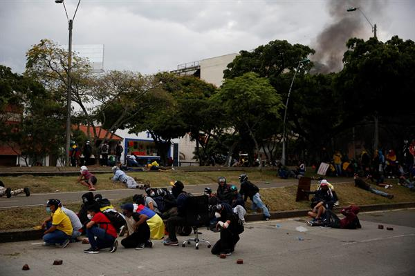 Manifestantes se cubren durante un enfrentamiento con la policía, en una jornada de protestas el 28 de mayo de 2021 en Cali (Colombia). EFE