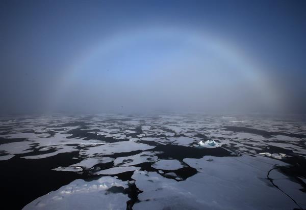 Un arco iris apareciendo en el horizonte en el Ártico.