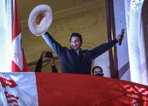El candidato izquierdista a la presidencia de Perú Pedro Castillo saluda a seguidores desde un balcón de la sede de su partido Perú Libre. EFE
