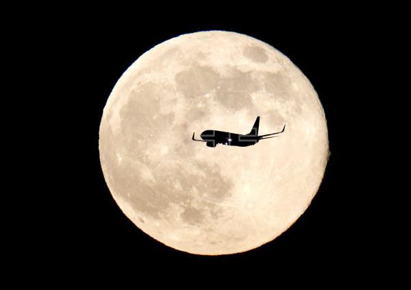 Un avión sobrevuela el cielo con la Luna de fondo. Foto: EFE