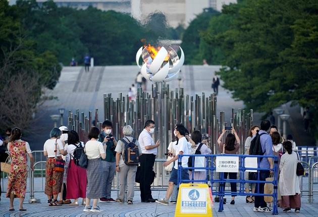 Personas se toman fotos con la Llama Olímpica en Tokio, Japón, que hoy registró nuevo récord de casos diarios de covid-19. Foto: EFE