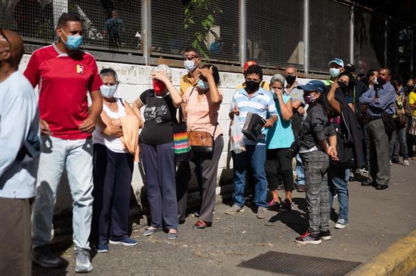 Personas hacen fila para ingresar a un centro de vacunación, en Caracas. EFE