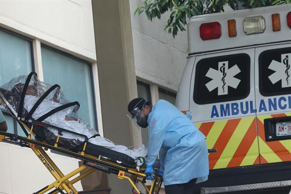 Personal de salud traslada a una persona contagiada con la covid-19 en la zona de emergencias del Hospital General , en la Ciudad de México. EFE