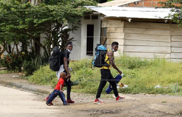 Migrantes caminan por la localidad colombiana de Necoclí, en la frontera con Panamá. Foto: EFE