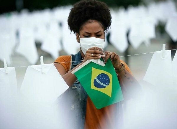 Una voluntaria ayuda a colgar pañuelos blancos durante un homenaje a las miles de víctimas mortales de covid-19 en Río de Janeiro, Brasil, el 8 de octubre de 2021. Foto: EFE